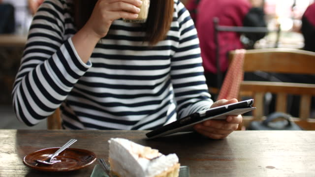 Close up Young woman Using Tablet PC and Drinking latte Coffee in Cafe, 4k (UHD)