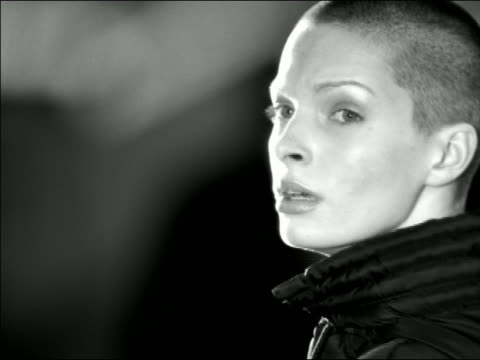 b/w close up young woman with shaved head turning head over shoulder to look toward camera - human head stock videos & royalty-free footage