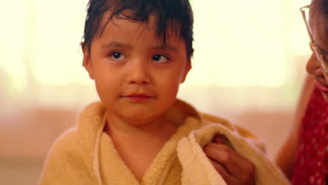 close up young woman with towel rubbing head of young native american boy smiling at camera - wet hair stock videos & royalty-free footage