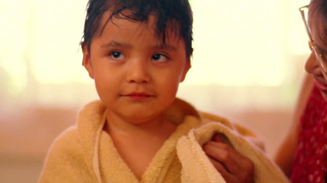 close up young woman with towel rubbing head of young Native American boy smiling at camera