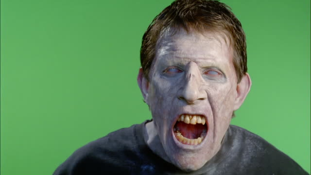Close up zombie looking at camera / grimacing / green screen