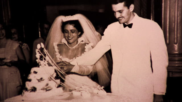 B/W close up zoom in archival photograph of bride + groom cutting cake at wedding