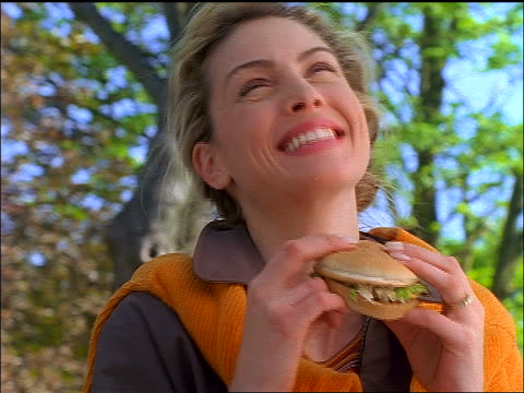 close up zoom in blonde woman smiling + laughing at camera + eating hamburger - 1997 stock-videos und b-roll-filmmaterial