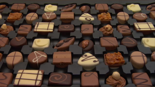 close up zoom in box of chocolates - table top shot stock videos & royalty-free footage