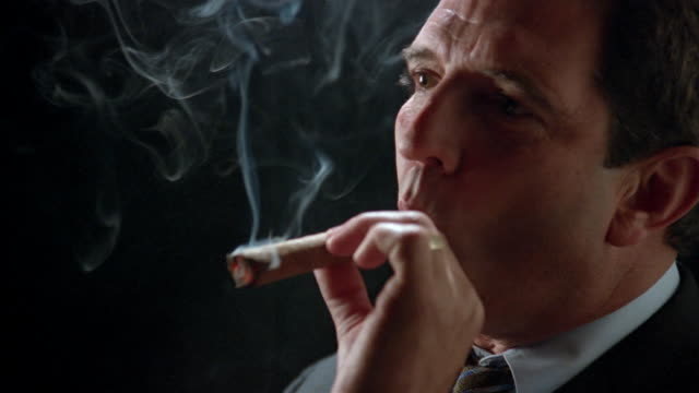close up zoom in businessman puffing on cigar/ zoom in taking cigar out of mouth, looking at camera and smiling - sigaro video stock e b–roll