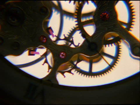 close up zoom in clock gears moving with white background - clockworks stock videos & royalty-free footage