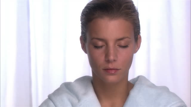 close up zoom in face of woman with wet hair wearing bathrobe with her eyes closed / opening eyes and looking at camera / blinking - wet hair stock videos & royalty-free footage