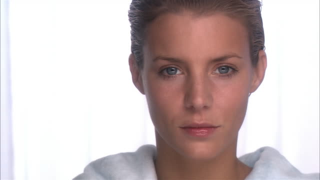 close up zoom in face of woman with wet hair wearing bathrobe with her eyes closed / opening eyes and looking at camera / blinking - bathrobe stock videos & royalty-free footage