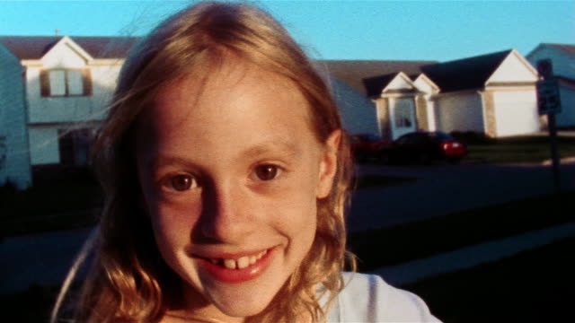 close up zoom in face of young girl with houses in background - wichita stock-videos und b-roll-filmmaterial