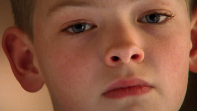 vídeos de stock e filmes b-roll de close up zoom in from face of serious young boy to his eye - sadness