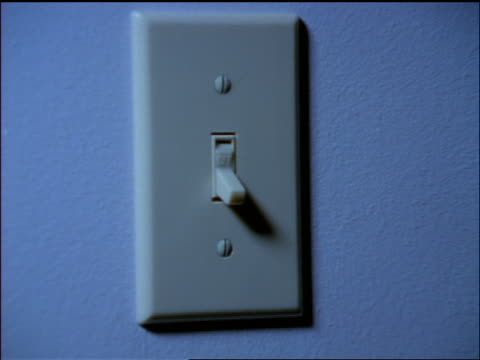blue close up zoom in hand of woman switching on light switch - light switch stock videos & royalty-free footage