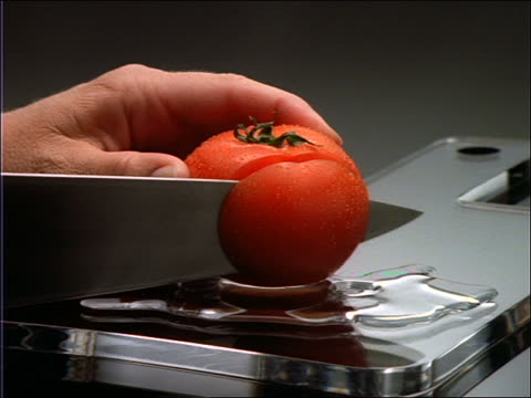 close up zoom in of hands slicing tomato with knife - tomato stock videos & royalty-free footage