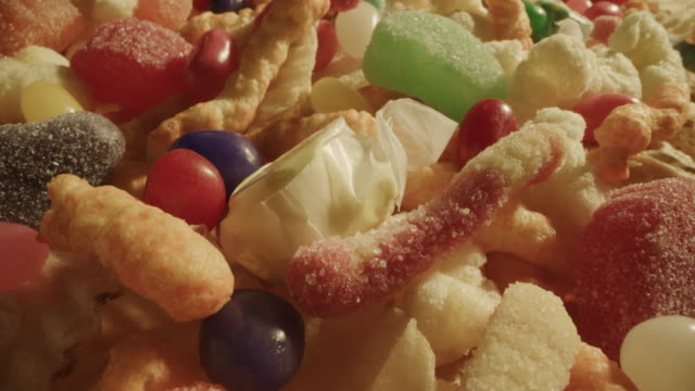 close up zoom in of variety of snack food chips and candy / cedar hills, utah, united states - ジェリービーンズ点の映像素材/bロール