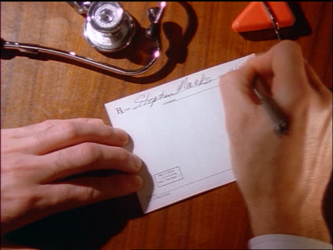 close up zoom in overhead hands of male doctor writing out prescription on desk - writing stock videos and b-roll footage