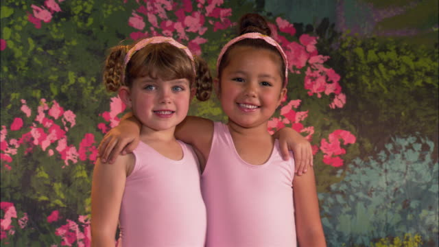 close up zoom in portrait of two ballerinas embracing and smiling - elementary age stock videos & royalty-free footage
