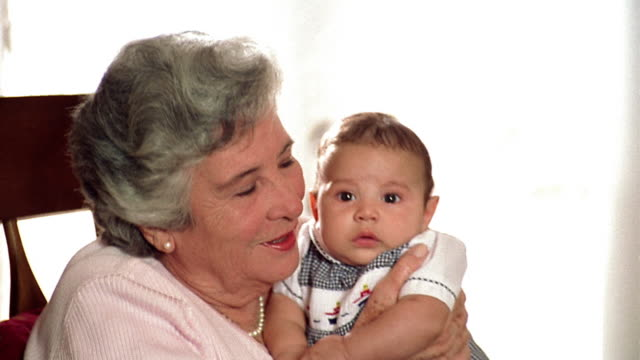 overexposed close up zoom in portrait senior hispanic woman holding + kissing baby boy indoors - overexposed video stock e b–roll