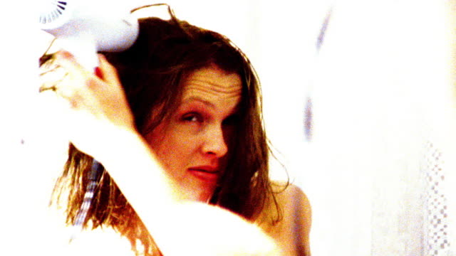 OVEREXPOSED close up zoom in reflection in mirror of woman blow drying hair after shower in bathroom