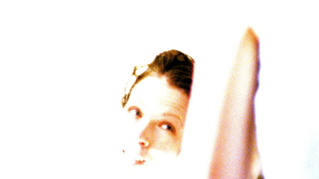 OVEREXPOSED close up zoom in reflection in mirror of woman drying hair with towel after shower in bathroom