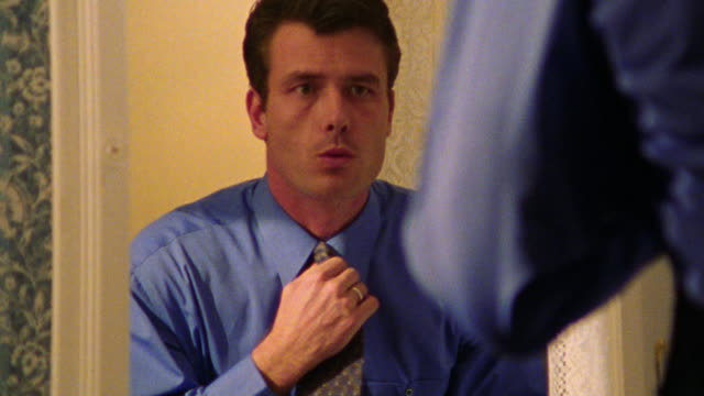 close up zoom in reflection of man adjusting tie in mirror - necktie stock videos & royalty-free footage