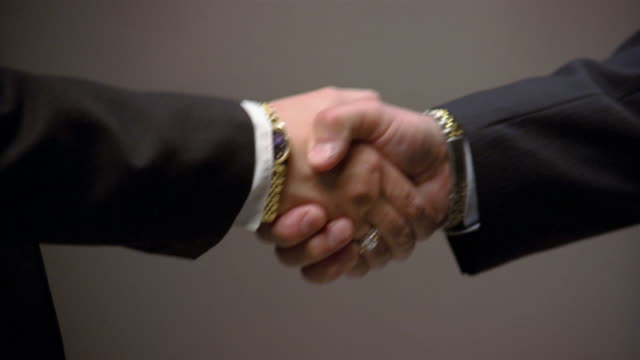 Close up zoom in shaking hands of businessman and businesswoman with large watches