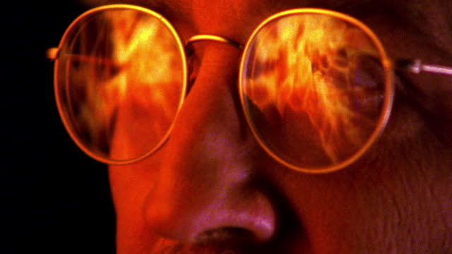 close up zoom in to extreme close up reflection of fire in eyeglasses of man with mustache