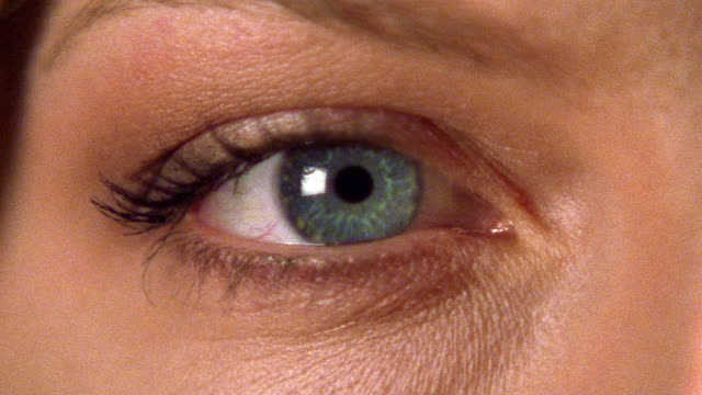 close up zoom in to extreme close up woman's blue eye blinking - eyelid stock videos & royalty-free footage