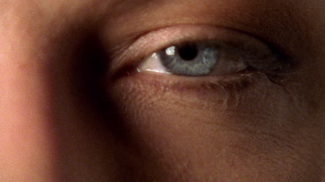 close up zoom in to extreme close up woman's blue eye opening - augen geschlossen stock-videos und b-roll-filmmaterial