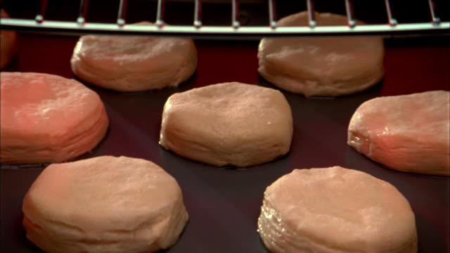 close up zoom in to time lapse biscuits baking and rising in oven - proofing baking technique stock videos and b-roll footage
