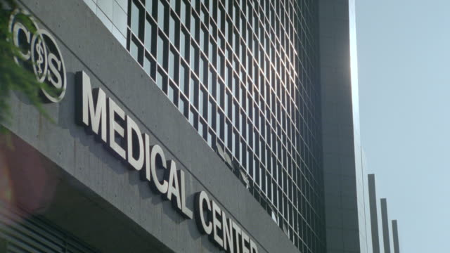 Close up zoom in to windows of building with 'Medical Center' sign on facade