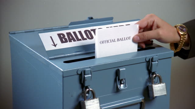 close up zoom in woman inserting ballot into ballot box - voting stock videos & royalty-free footage