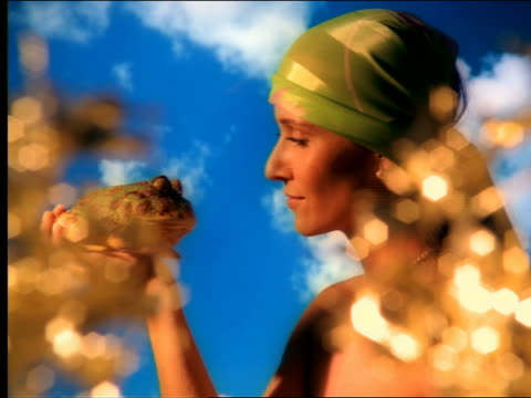 close up zoom in woman wearing scarf on head leaning in + kissing fake frog in studio with cloud backdrop - prince stock videos & royalty-free footage