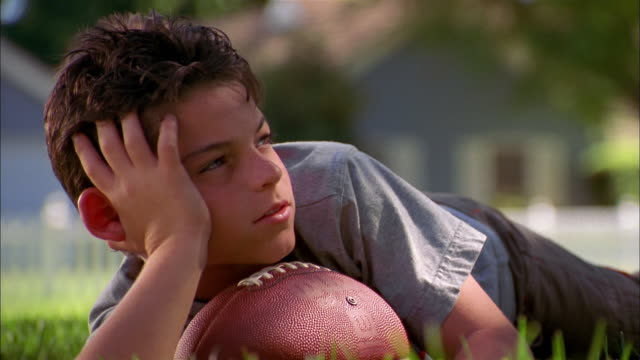 close up zoom in young boy lying outdoors w/football and looking at cam - negative emotion stock videos & royalty-free footage