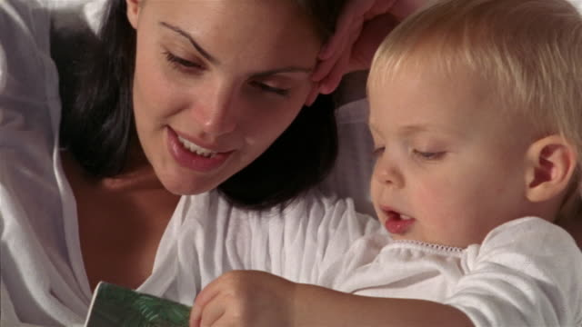 vidéos et rushes de close up zoom in zoom out mother and child reading storybooks together in bed / mother closing eyes and resting - parents