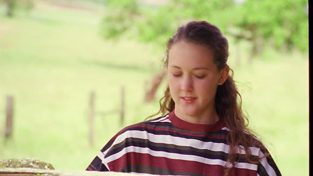 close up zoom in zoom out portrait teen girl standing by fence smiling + nodding at camera (flash frames) - one teenage girl only stock videos & royalty-free footage
