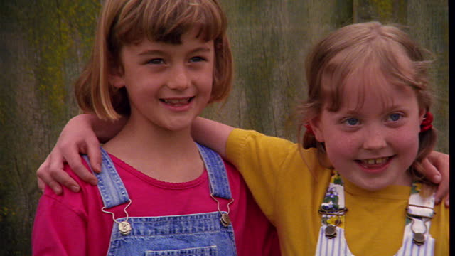 close up zoom in zoom out portrait two girls standing with arms around each other talking, screaming + laughing - dungarees stock videos and b-roll footage