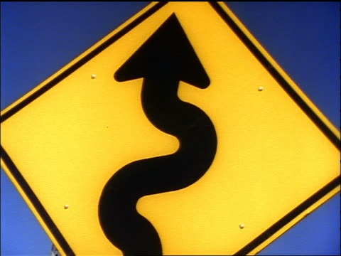 close up zoom in + zoom out winding road warning sign / blue sky in background - anno 1998 video stock e b–roll
