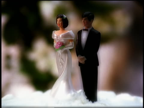 close up zoom out chainsaw cutting through wedding cake with miniature plastic bride + groom - 離婚点の映像素材/bロール