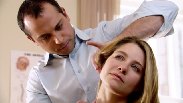 Close up zoom out chiropractor adjusting woman's neck