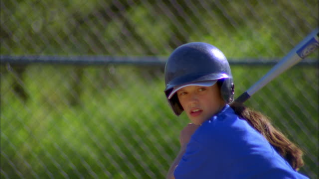 close up zoom out girl swinging bat and hitting ball in baseball game - baseballspieler stock-videos und b-roll-filmmaterial
