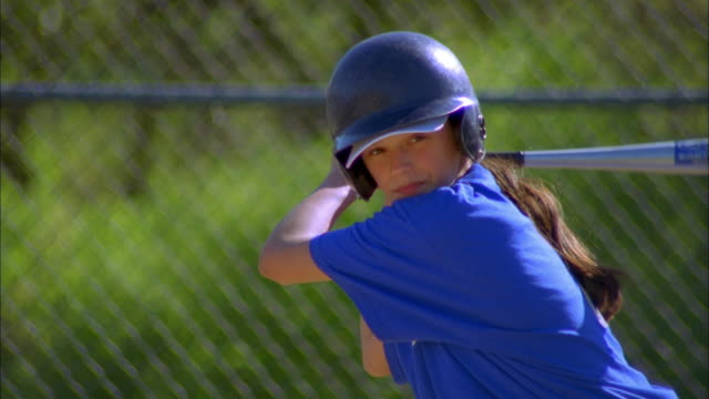 Close up zoom out girl swinging bat and missing ball in baseball game