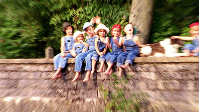 OVEREXPOSED close up zoom out group of children in overalls sitting on bridge waving to camera