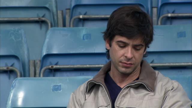 vídeos y material grabado en eventos de stock de close up zoom out man sitting in empty stadium and looking at watch/ england - soledad