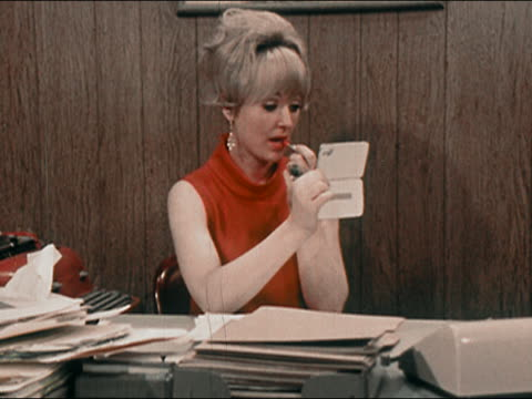 vidéos et rushes de 1969 close up zoom out medium shot secretary looking in compact mirror and applying lipstick at desk / getting up from desk - rouge à lèvres