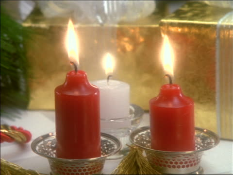 close up zoom out of lit candles + christmas gifts on table - medium group of objects stock videos and b-roll footage