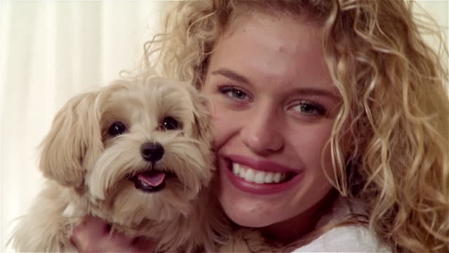 close up zoom out portrait girl holding maltese-toy poodle mix - pampered pets stock videos and b-roll footage