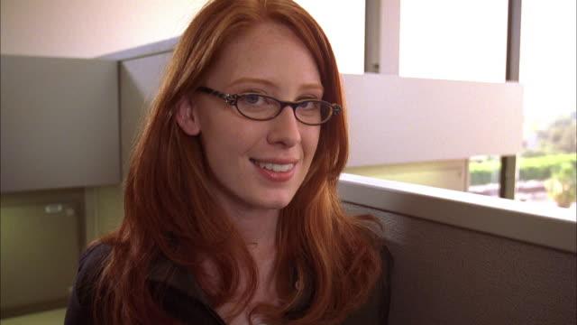 vídeos y material grabado en eventos de stock de close up zoom out portrait of female office worker w/red hair and eyeglasses standing by cubicle - 30 39 años