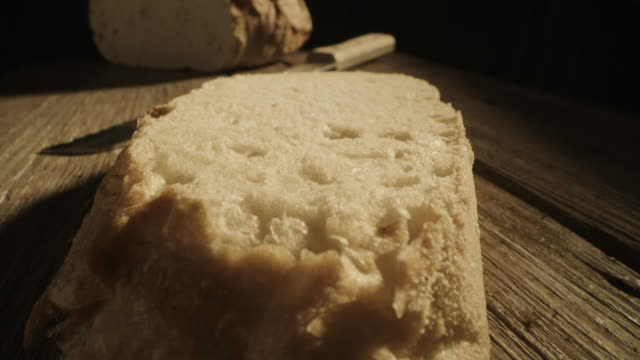 close up zoom out revealing slice of bread on wood table / cedar hills, utah, united states - loaf of bread stock videos & royalty-free footage