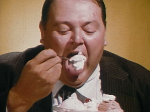 1966 close up zoom out smiling fat man eating ice cream dessert / AUDIO