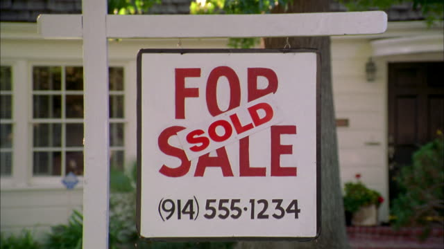 close up zoom out 'sold' banner on 'for sale' sign in front yard of house - tyre swing stock videos & royalty-free footage