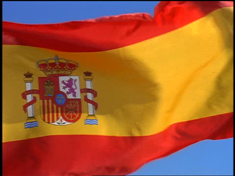 close up zoom out pan spanish flag blowing in wind / blue sky in background - spanish flag stock videos and b-roll footage